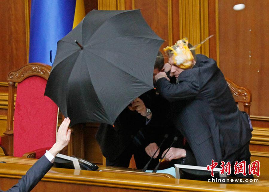 图为议长藏在伞后躲避不断飞来的鸡蛋。