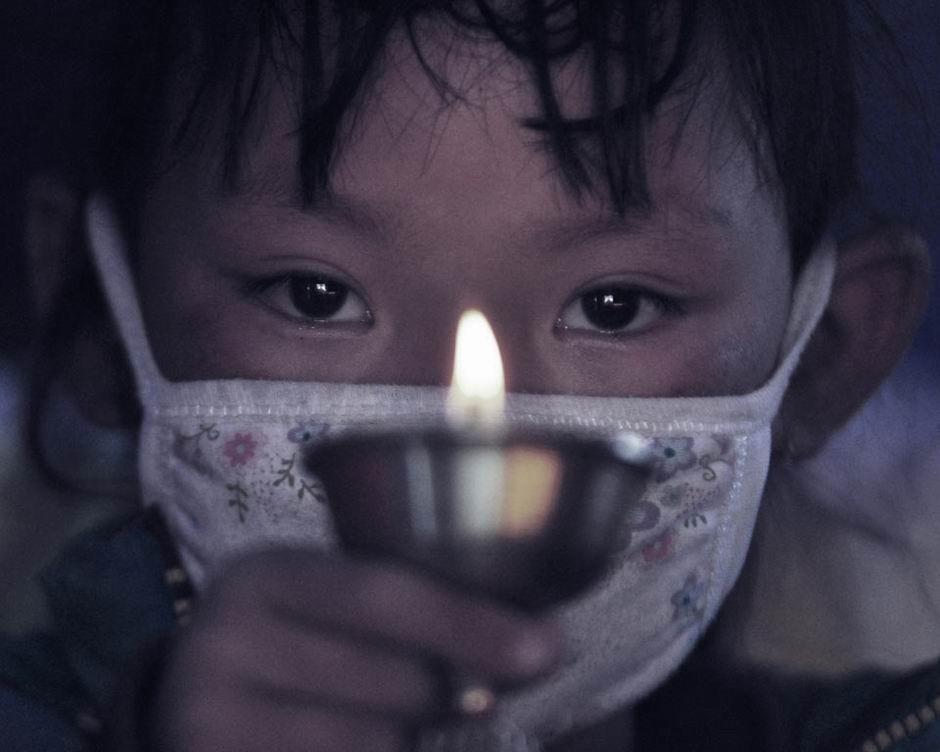 4月27日,玉树县新建北路,8岁的扎西拉毛点起点酥油灯,为在地震中遇难的亲人祈祷。