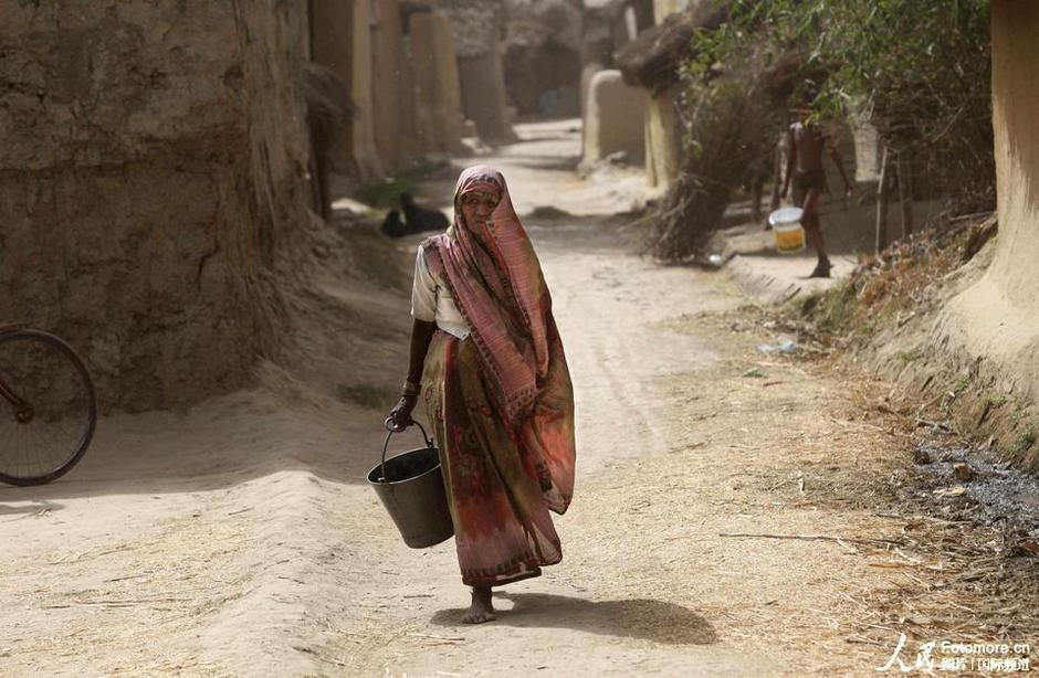 5月25日,印度,阿姆利策:一位印度妇女提着水桶去取水。