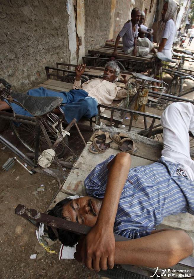5月27日,印度,阿拉哈巴德:人们在街边休息乘凉。