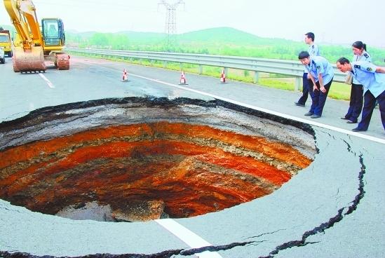 图为高速公路上突然塌陷的深坑。摄影:浙江新闻网/林邦