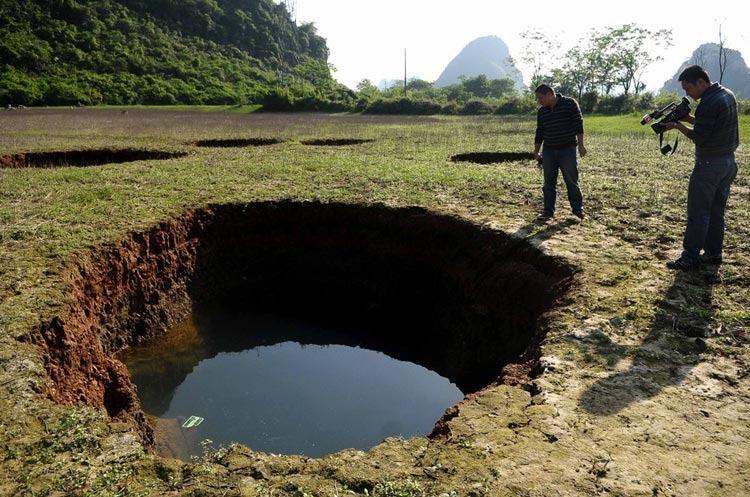 """4月8日,媒体记者在拍摄由地陷形成的""""天坑""""。"""