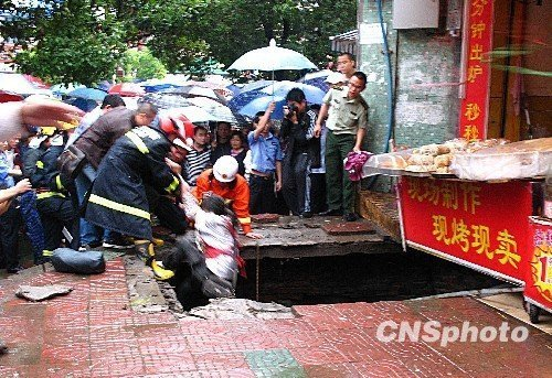 图为消防人员将伤者拉出大坑。