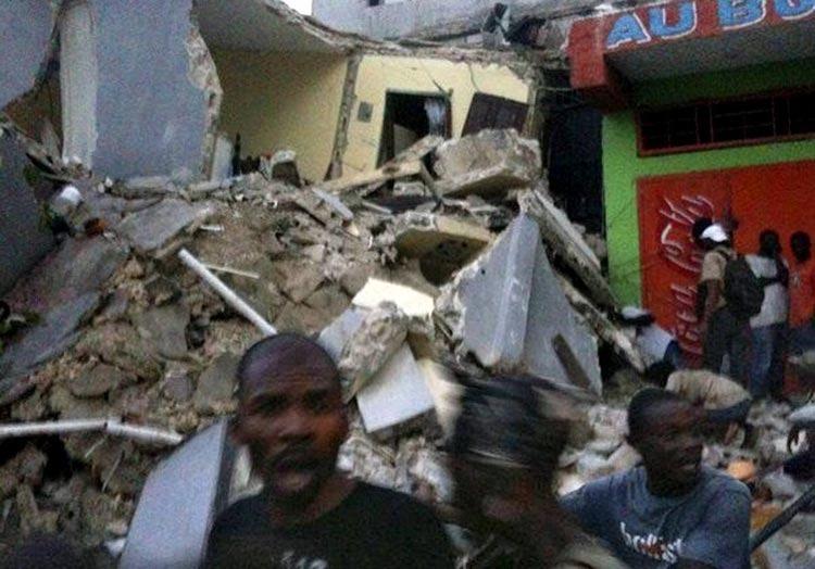 1月12日,在海地首都太子港,人们站在倒塌的建筑物旁。