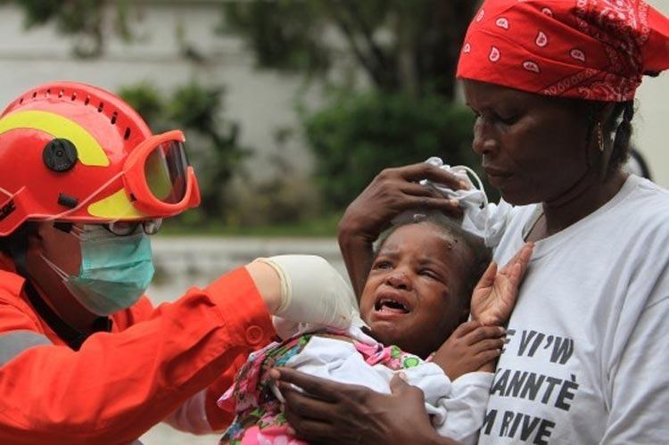 1月14日,中国国际救援队的医务人员在海地首都太子港为伤员进行治疗。新华社记者邢广利摄