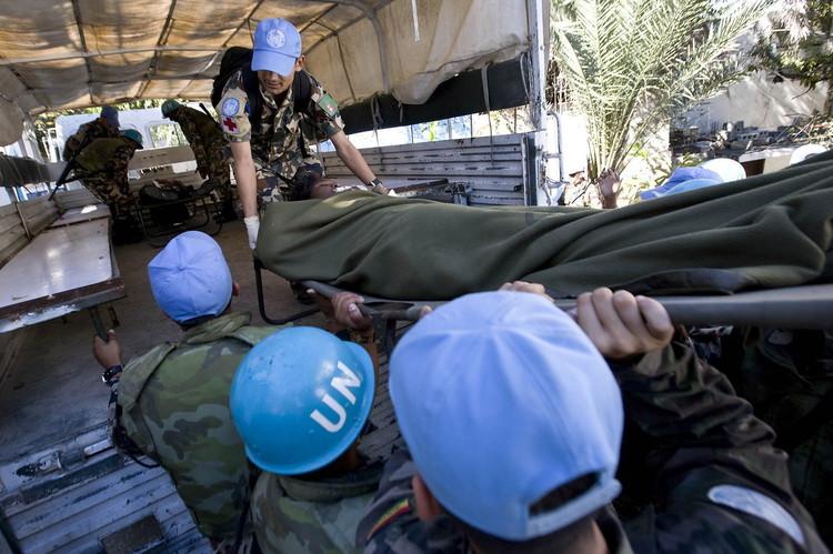 联合国维和部队工作人员将伤者台上卡车送往医院。