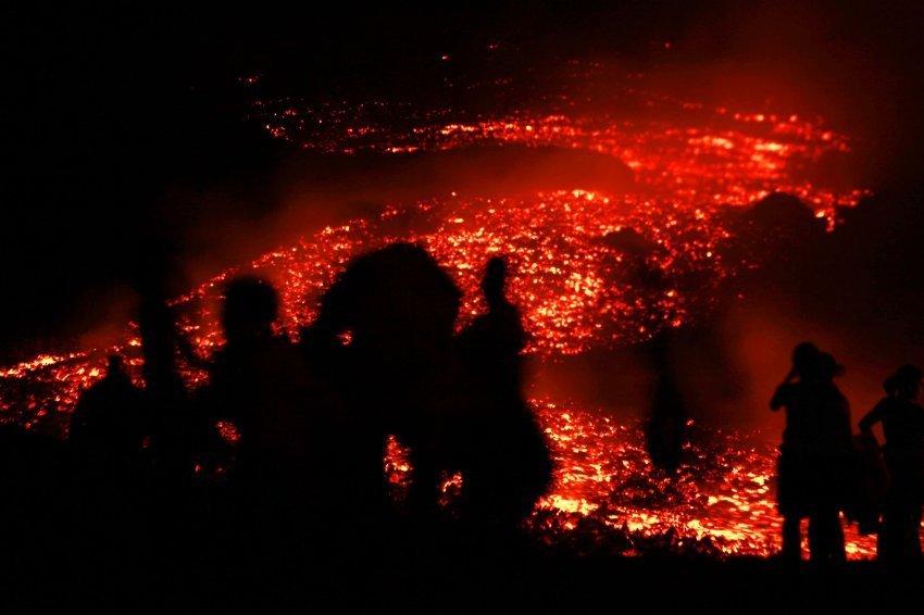 观光客站在危地马拉的帕卡亚火山前,数以千计的游客希望能近距离欣赏火山喷发美景。