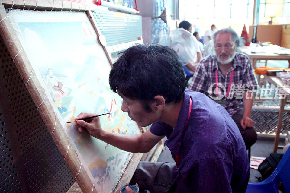 30岁的藏族小伙子西绕降村在宝钢大舞台一角仔细地绘制一幅唐卡。他的师父、国家一级美术师洛松向秋坐在身后观看。师徒二人似乎丝毫没有感觉到天气的炎热