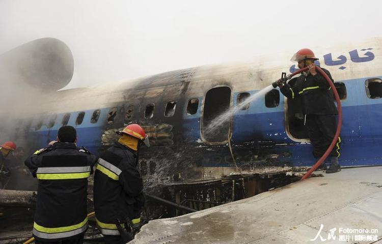 伊朗一架俄制客机降落时起火,消防员在扑灭飞机上的余火图片