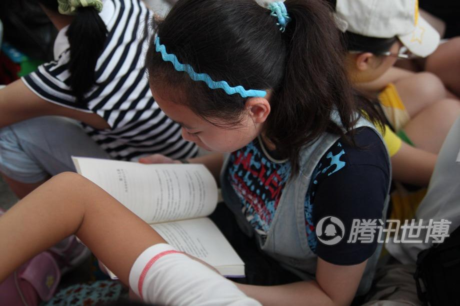 队伍当中,一位中学生一边排队一边看书