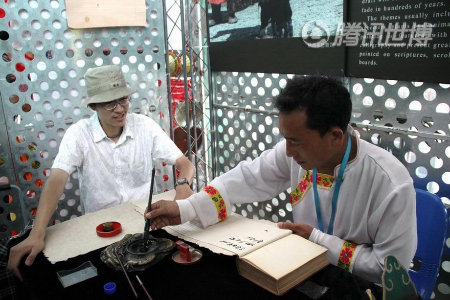 宝钢大舞台传习区,纳西族东巴画传承人和国耀正在自己的展位上为一名游客提笔书写东巴文字