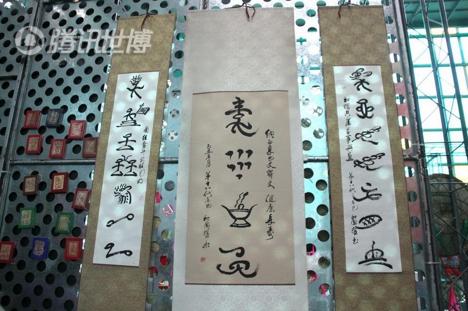 """位上悬挂的东巴字幅,左边的意思是""""团结奋斗 前程光明"""",右边是图片"""