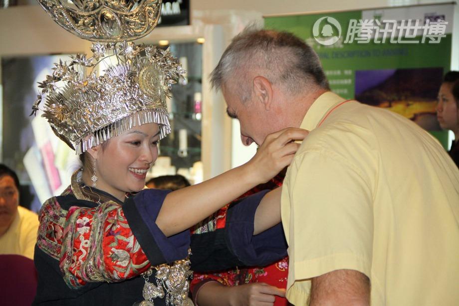 苗族姑娘为一位外国游客戴上绣球