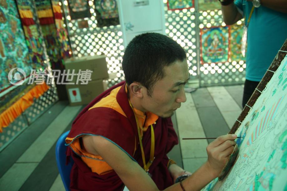 在宝钢大舞台,甘肃活动周唐卡传习现场,洛藏东周正在认真绘制唐卡