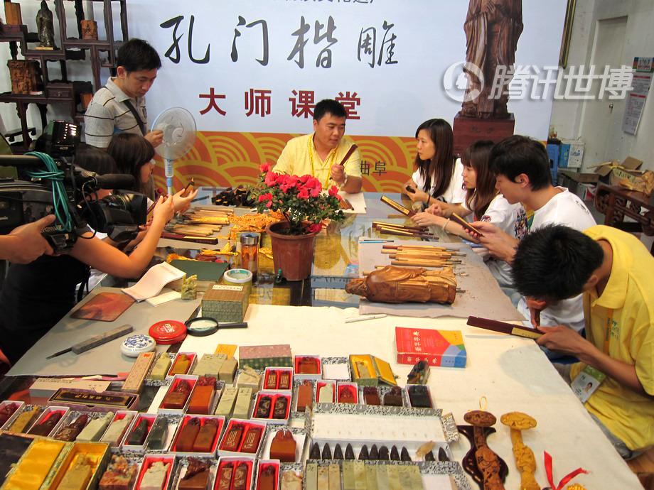 在孔门楷雕的展位内设有大师课堂,游客可以亲自动手雕刻