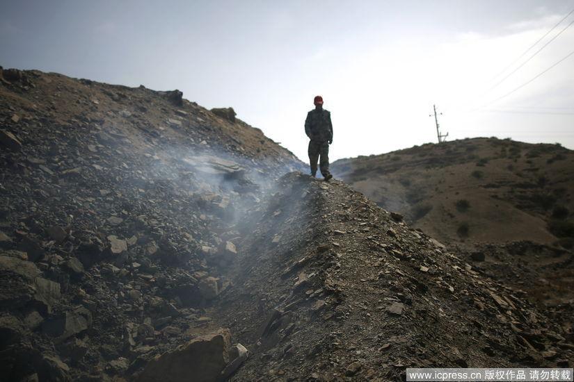 2010年9月5日,一位灭火队员从一处矿山着火点上走过