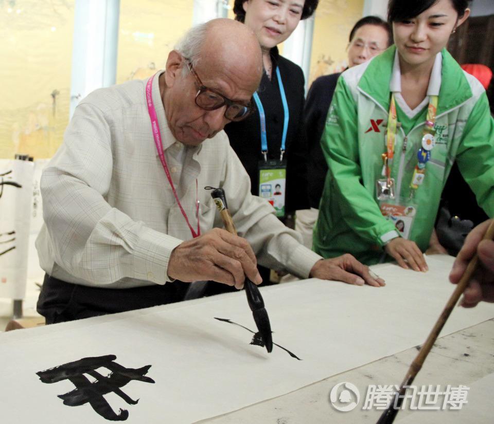 对面的游人也拿起旁边的毛笔和老人一起写字