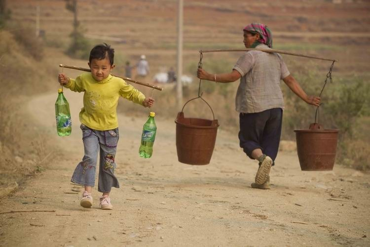 纪录类+优秀作品+云南大旱(组2)+鲁海涛+2010年3月23日,云南石林县大石桥村,6岁女孩杨云润取水后挑着两桶水回家,她需要走完这段300米的土坡才能到家。政府的消防运水车每天下午5时准点将生活用水送在大石桥村的村口。