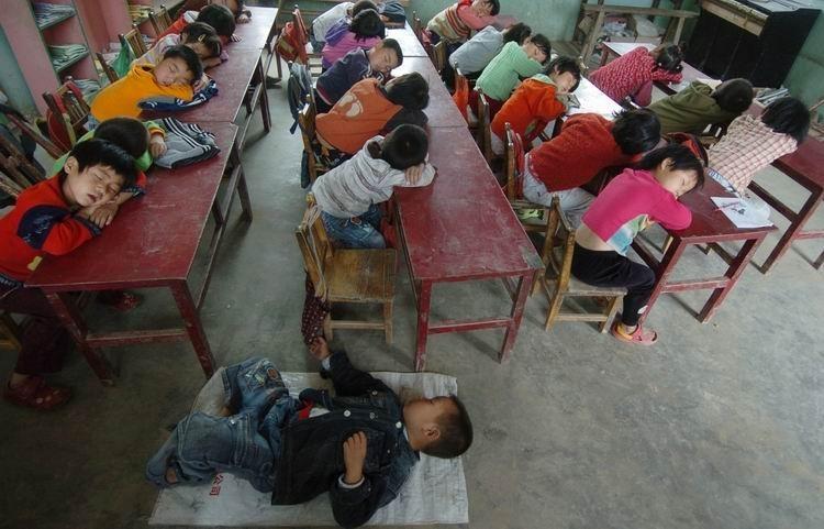 纪录类+优秀作品+教室午休+江宏景+2007年5月31日,山西省芮城县风陵渡镇六官学校,小学生们在午休。该校是一所全日制公立小学,由于许多学生离家较远,以及这所学校处于偏远的欠发展山区,校舍简陋,没有宿舍,在教室午休就成了这所学校的传统。据调查,这里很多农村小学由于条件所限,打地铺或者伏案午休成了传统。