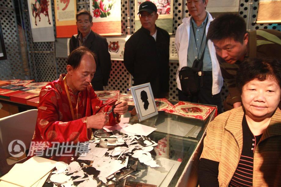 老艺术家魏海正在给游客剪头像