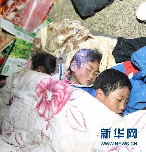 2010年4月14日深夜,几名受灾儿童在露天睡觉,他们的父母正在旁边搭建帐篷。 当日7时49分,青海省玉树藏族自治州玉树县发生7.1级地震,给当地人民群众生命财产造成严重损失。丁林 摄