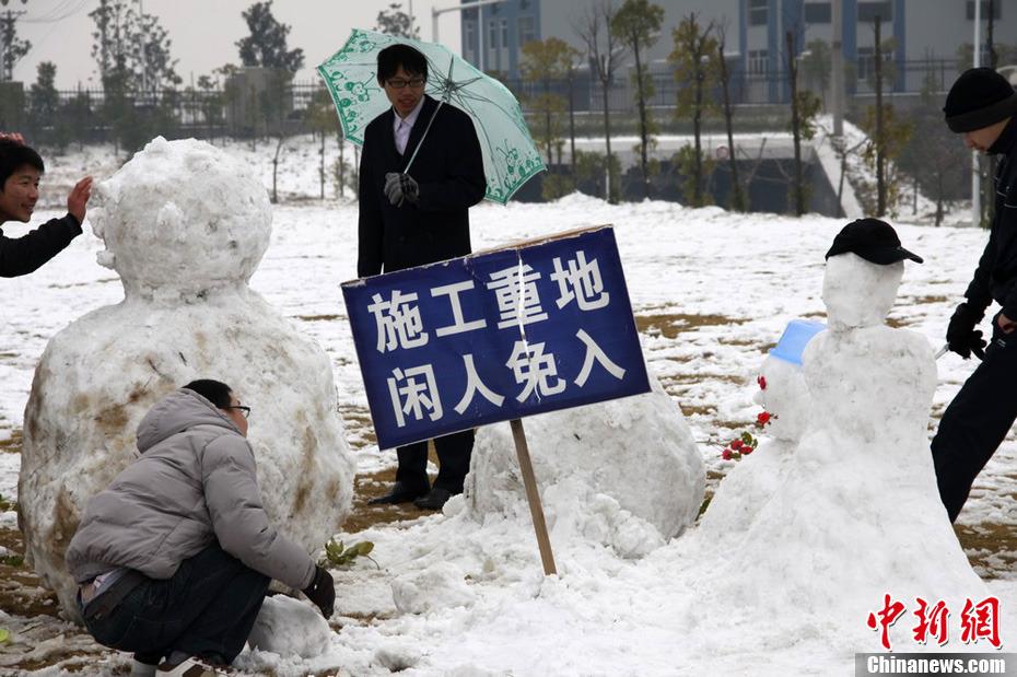 """新年伊始,湖南三湘大地普降瑞雪,天空中飘飘洒洒的洁白雪花,给人们带来了新年喜悦。湖南气象部门统计显示,1月2日8时至3日8时,湖南大部分地区出现了小到中雪,湘中以南局部地区出现了大到暴雪,且出现了不同程度的积雪,益阳、株洲、临湘积雪深度最大为6厘米。图为长沙市民纷纷走出室内,在雪地里嬉戏堆雪人,在""""施工场地""""还竖起了""""施工重地闲人免入""""牌子。 中新社发 刘柱 摄"""