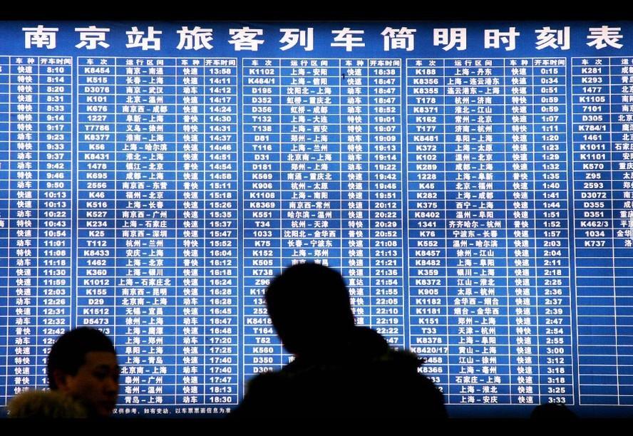 1月9日,旅客在南京火车站售票大厅查看列车时刻表。当日,2011年春运首日(1月19日)火车票开始发售。