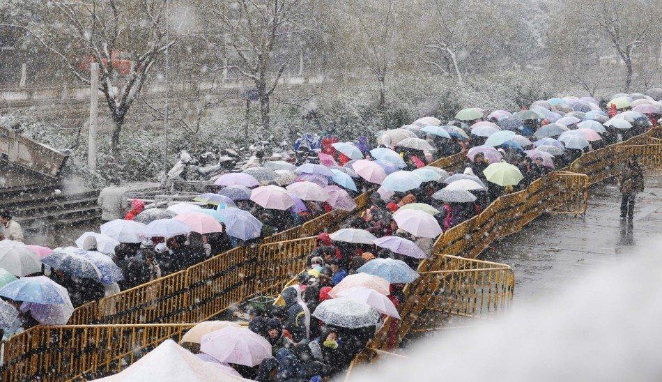 1月18日,众多旅客冒雪在设立于江苏省苏州市体育中心体育场的集中售票处外排队,准备购买火车票。 新华社发(朱桂根 摄)