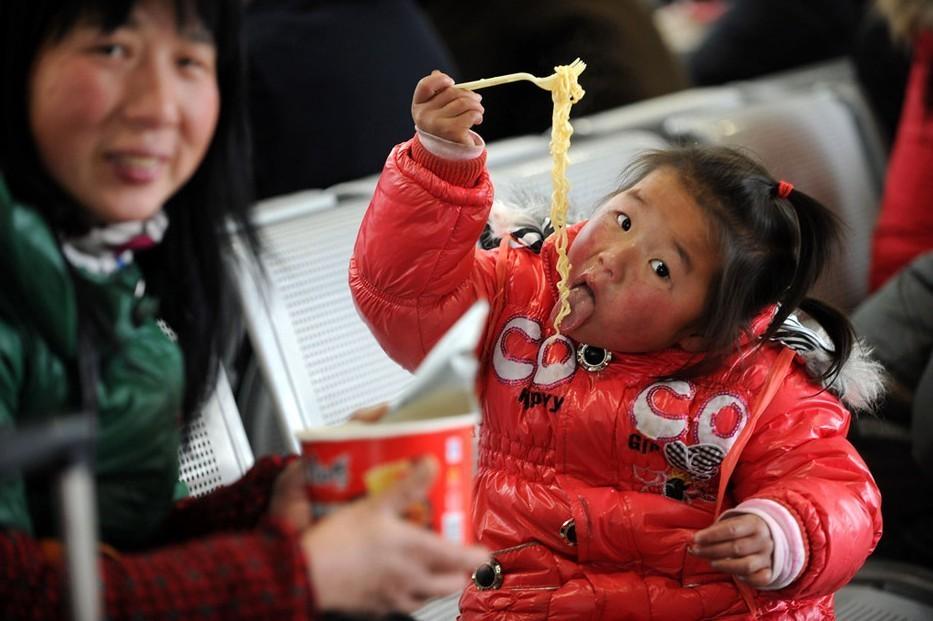 1月19日,与妈妈一同前往深圳过年的余明丽小朋友在合肥火车站候车室吃方便面。