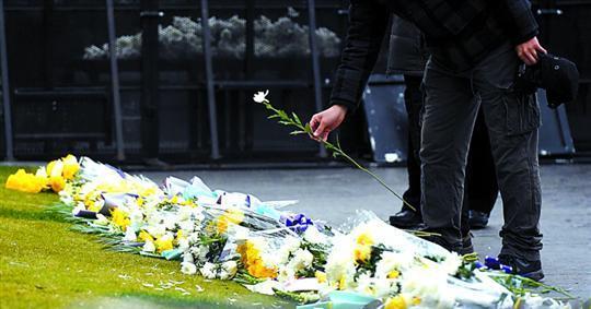 一名吊唁外滩拥挤踩踏事件遇难者的市民用一枝白菊寄托哀思。