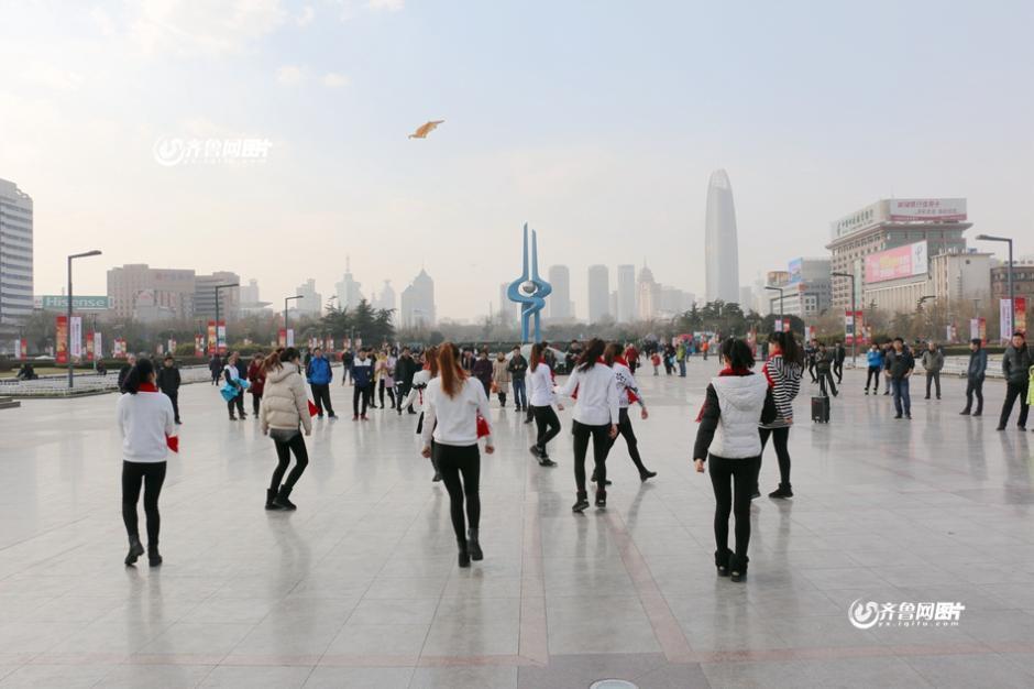 2015年1月23日讯,在济南泉城广场,山东体育学院的女生在蓝天白