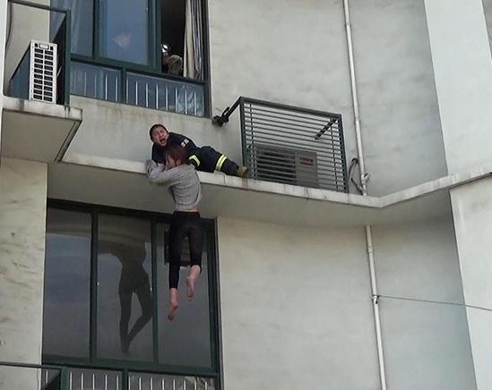 轻生女子仅靠双手抓窗檐维持平衡,为防止女子坠楼,消防员来不及佩戴规定安全措施,直接翻窗营救。