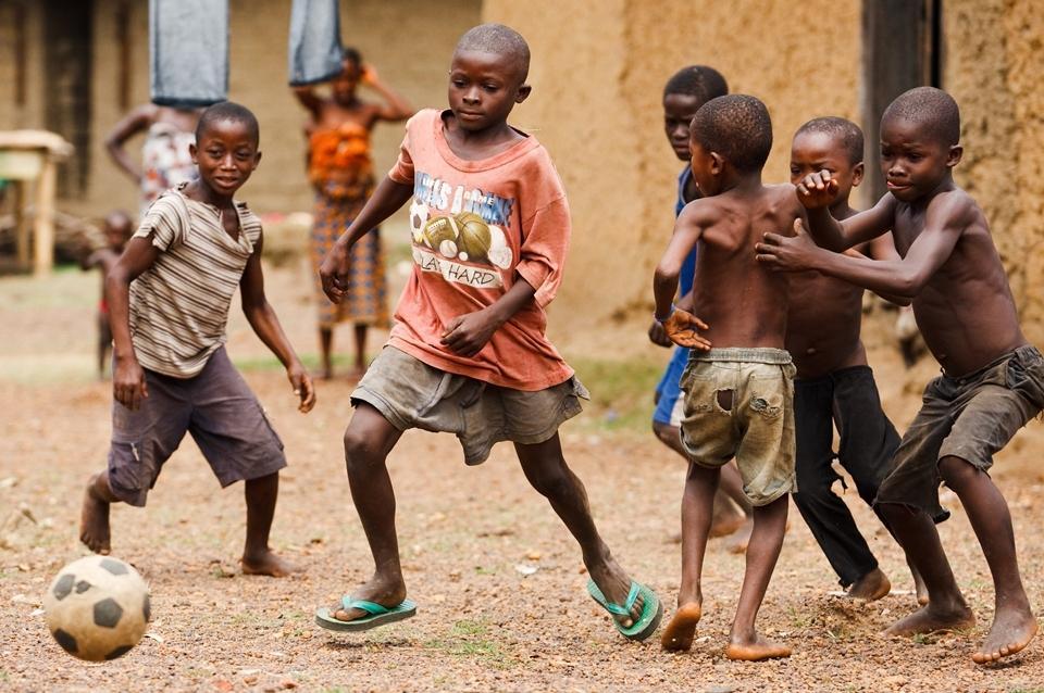 蓬丹布村的一群小朋友在踢足球.中间的男孩说他曾经上过学,可