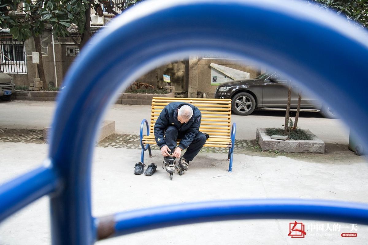 在楼道下的空地,刘爷爷坐在椅子上更换轮滑鞋.