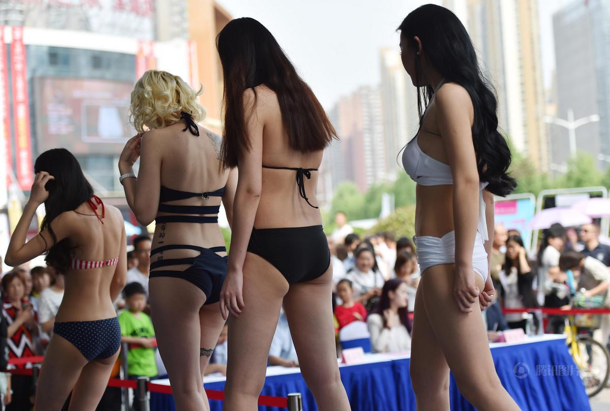 """选手在进行泳装展示 ,一名外国选手的身上刺着""""生命的一瞬间""""汉字文身。"""