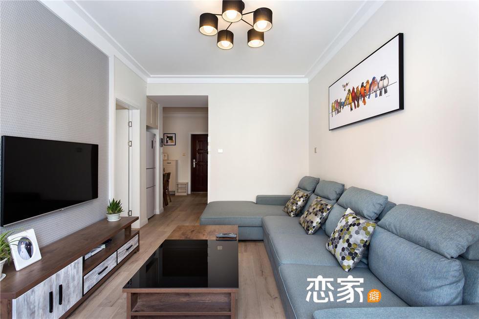 蓝色布艺沙发,木质的茶几和电视柜,整个墙面都为白色,空间明亮.图片