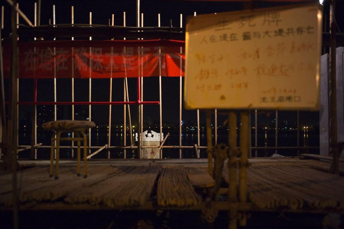 抗洪标语贴满沿线的值班点、渣土车以及江滩墙面,生死牌悬挂在值