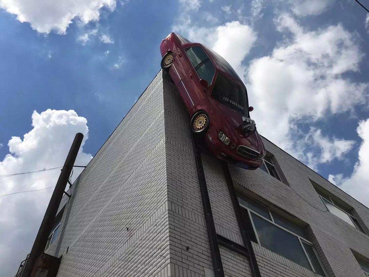 长春男子把轿车倒挂在3层楼墙面 让人大开眼界