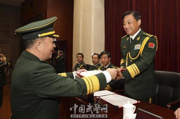 走到主席台前.武警部队司令员王宁、政委孙思敬等领导分别为他图片