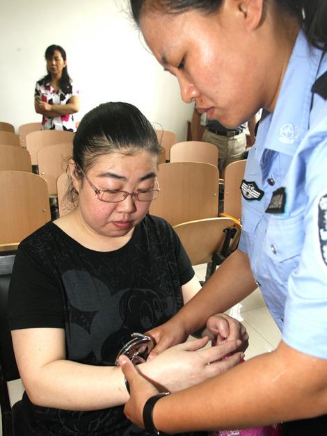 6月9日,法警给被告人王亚丽戴上手铐.新华社发 -高清