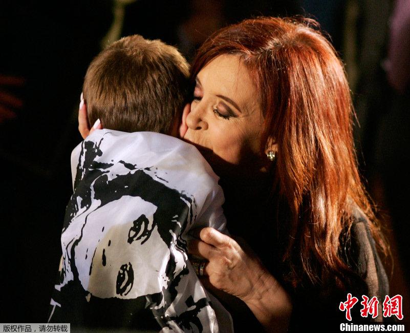亲吻一名披着印有她头像旗帜的孩子.阿根廷现任女总统、阿根廷执