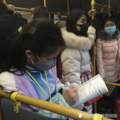 坐公交车回家的女学生站着写作业
