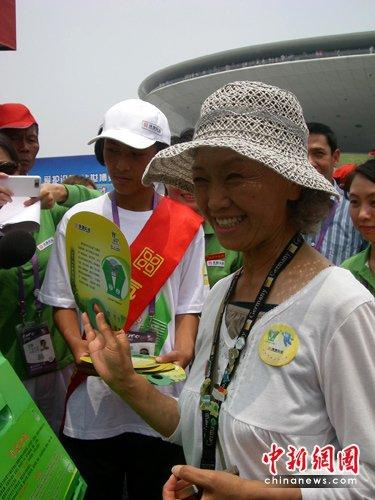 """23日,有""""世博奶奶""""之称的61岁山田外美代在上海世博园世博文化中心向游客示范如何将垃圾分类投放,更好地保护世博园环境整洁。出生日本的山田外美代因为对世博会的狂热喜爱而声名远播,她曾创下爱知世博会185天进场243次的纪录,上海世博会开幕50多天来每天都可以看到她的身影,山田外美代在上海世博会的目标同样是""""184天全勤""""。"""