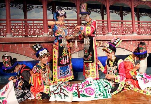 5月11日,7位来自四川阿坝州茂县的羌族女孩为游客表演羌绣,以表达对全国人民支持灾区的感恩之情和灾区群众自强不息、重建美好家园的心情。新华社记者 凡军 摄