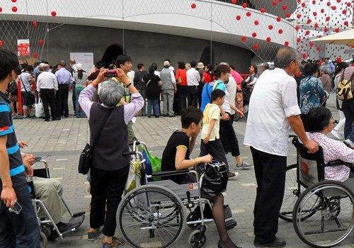 网友曝世博最牛轮椅女 单脚踩地通过特殊通道