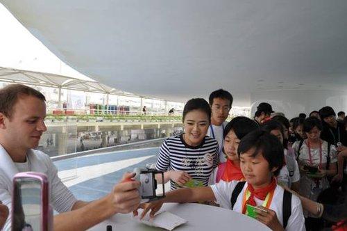 """丹麦国家馆工作人员为参与""""明星带你看世博""""活动的儿童盖章。"""