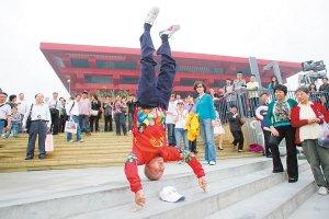 图文:南京86岁老人二指倒立和中国馆合影