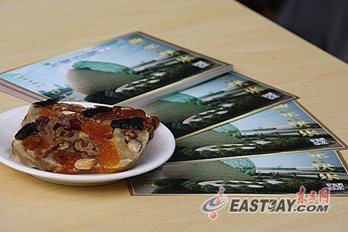图片说明:干果蛋糕成品以及印有干果蛋糕食谱的新年贺卡摆放在桌上