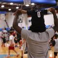 组图:利拉德现身篮球训练营 身背儿童亲密互动