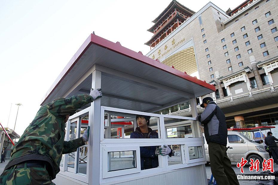 12月21日,北京西站北广场工作人员安装验票亭.自2012年1月1日